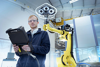 Portrait of engineer with robot in robotics research facility - p429m1547590 by Monty Rakusen