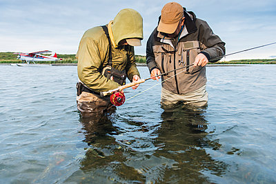 Fly fisherman and guide prepare for the next cast in Ugashik River, Southwest Alaska, USA - p442m1451106 by Carl Johnson