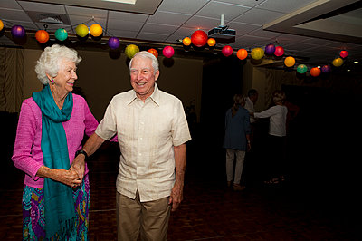 Older Caucasian couple dancing at party in retirement home - p555m1408809 by Shestock