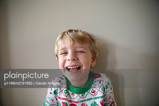 Close Up Portrait of Laughing Boy in Red and Green Christmas Pajamas - p1166m2191953 by Cavan Images