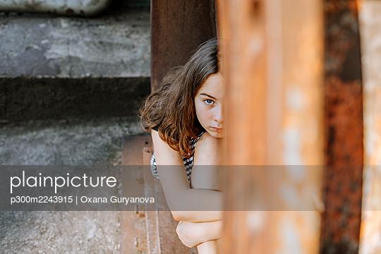 Teenage girl hugging knees while sitting on abandoned window sill - p300m2243915 by Oxana Guryanova