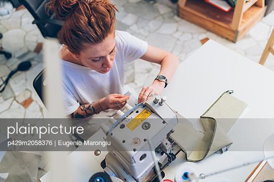 Fashion designer working at sewing machine - p429m2058376 by Eugenio Marongiu