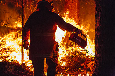 A firefighter conducting a controlled burn with a drip torch - p1166m2193726 by Cavan Images
