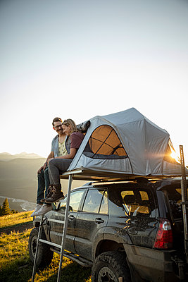 Affectionate couple relaxing at SUV rooftop tent in idyllic mountain field - p1192m2016497 by Hero Images