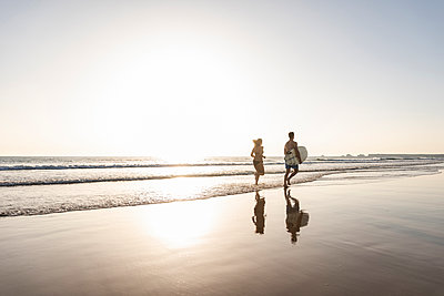 Young couple running on beach, carrying surfboard - p300m2043053 by Uwe Umstätter