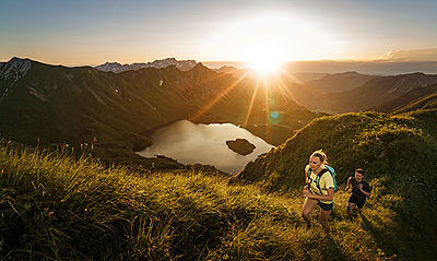 Germany, Allgaeu Alps, man and woman running on mountain trail - p300m2062044 by Matthias Aletsee