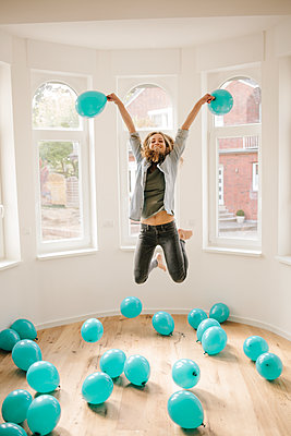 Young woman in new apartment playing with balloons - p586m1064896 by Kniel Synnatzschke
