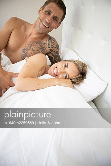 Couple in love lying in bed - p1640m2259589 by Holly & John