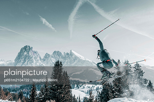 A skier jumping and raising snow with the Sassolungo in the background in the Alpe di Siusi valley on a sunny winter afternoon - p651m2104722 by Maurizio Rellini