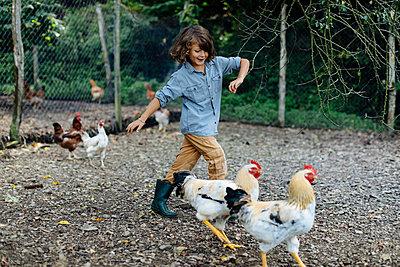 Boy chasing chickens on an organic farm - p300m2144733 von Sofie Delauw
