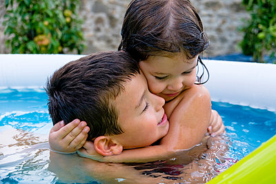Brother and his little sister hugging each other in swimming pool - p300m2189413 by Giorgio Magini