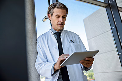 Mid adult male doctor using digital tablet while leaning on pole by glass window at hospital - p300m2273800 by Buero Monaco