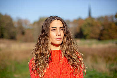 Young woman in red pullover outdoors - p975m2222126 by Hayden Verry
