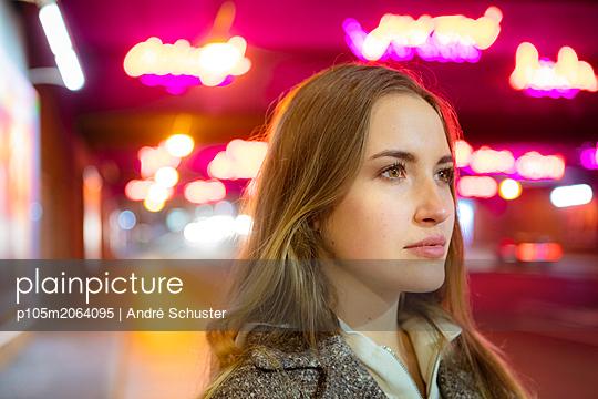 Junge Frau wartet an einer Straße in der Dämmerung - p105m2064095 von André Schuster