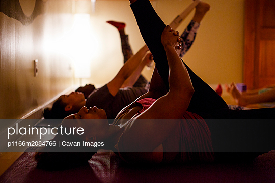 a small group of women practice stretches in a darkened room - p1166m2084766 by Cavan Images