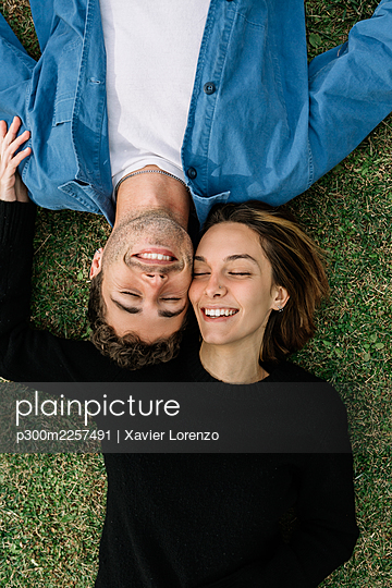 Smiling couple lying on lawn - p300m2257491 by Xavier Lorenzo