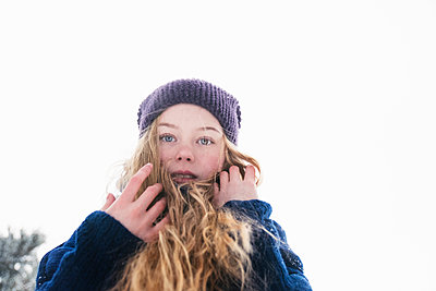 Low angle portrait of woman with blond hair standing against clear sky during winter - p1166m2025418 by Cavan Images