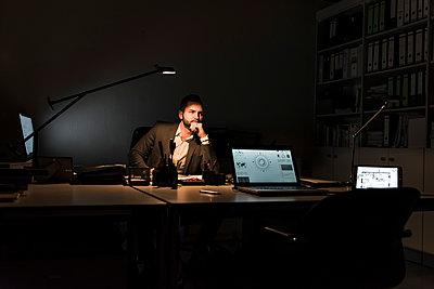 Pensive businessman sitting at desk in office at night - p300m1581532 von Uwe Umstätter