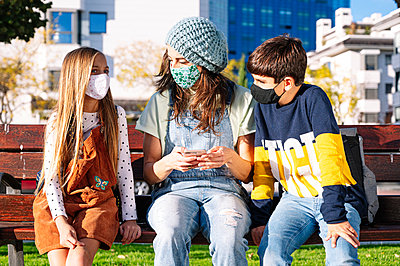 Mother and kids wearing protective face mask using smart phone sitting on bench in public park during sunny day - p300m2226489 by Jose Luis CARRASCOSA