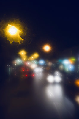 Defocused image of cars on city street at night - p301m1406540 by Michael Mann