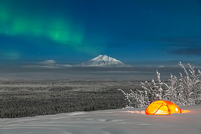 Green Aurora Borealis shines above moonlight casting light on Mount Drum and the Copper River Valley, a glowing tent on a foggy winter night, Copper River Valley, South-central Alaska; Alaska, United States of America - p442m1217828 by Kevin Smith