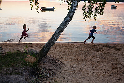 Two Children Running On The Beach In The Evening Sun, Sweden  - p847m1529351 by Mikael Andersson