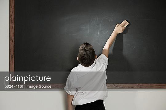 Boy cleaning blackboard - p9247416f by Image Source