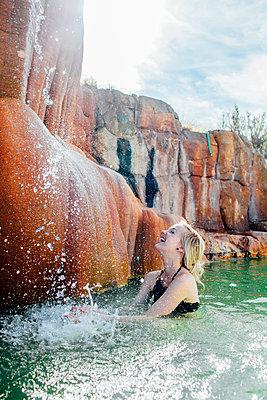 Cheerful woman splashing water in pond - p1166m1229409 by Cavan Images