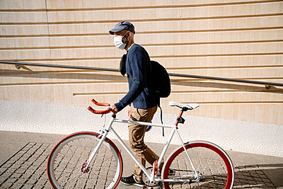Man with bicycle looking away while walking by wall on footpath during COVID-19 - p300m2264608 by Albert Martínez