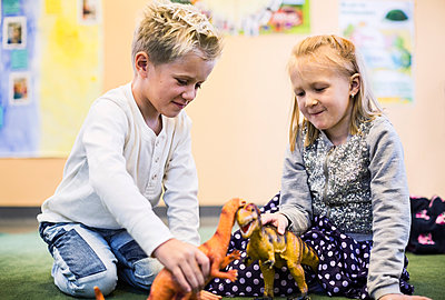 Kids playing with toy dinosaurs in kindergarten - p426m920165f by Maskot