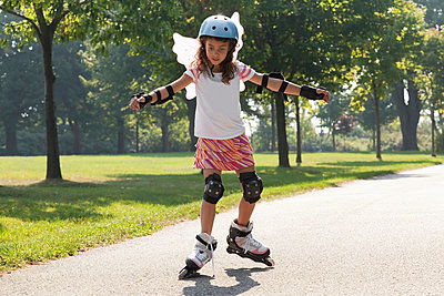 Young girl learning to inline skate while wearing fairy wings;Whitby ontario canada - p442m839774 by Mary Ellen McQuay