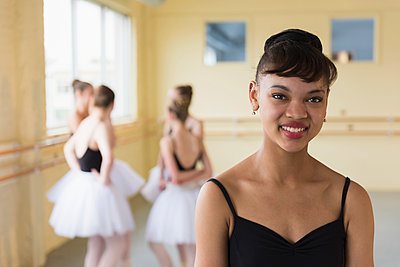Portrait of girl smiling in ballet studio - p555m1491099 by Mark Edward Atkinson