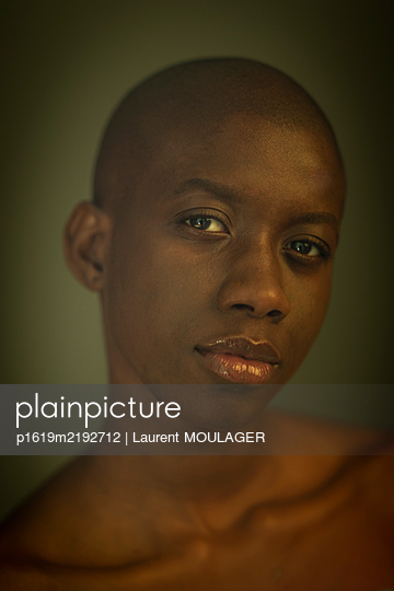 Portrait of a young black shaved woman looking a the camera - p1619m2192712 by Laurent MOULAGER