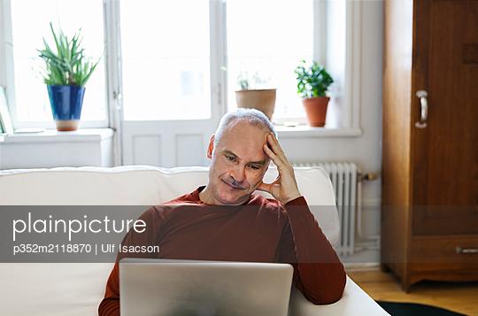 Senior man using laptop - p352m2118870 by Ulf Isacson