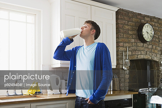 Young man drinking milk - p9249404f by Image Source