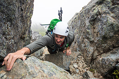 high angle view of climber reaching for a hand hold. - p1166m2147482 by Cavan Images