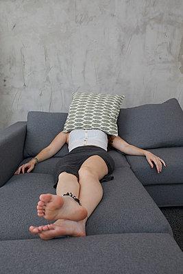 Frau versteckt sich unter einem Kissen  - p276m2115812 von plainpicture