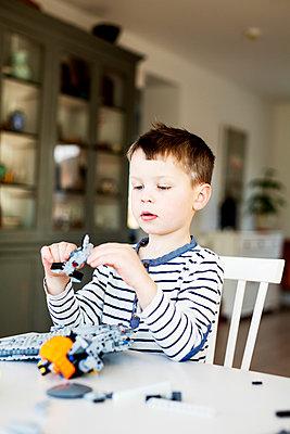 boy playing with lego - p312m1131469f by Malin Kihlstrom