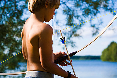 Shirtless boy holding bow and arrow - p312m695527 by Plattform photography