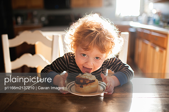 Toddler boy sitting at table licking a cinnamon roll at home - p1166m2137210 by Cavan Images