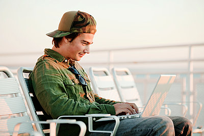 Man using laptop computer while sitting on deckchair in ship - p1166m985515f by Cavan Images