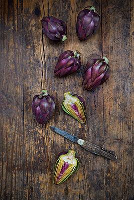 Sliced and whole purple organic artichokes and a pocket knife on dark wood - p300m1205565 by Larissa Veronesi