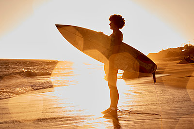 Young man holding surfboard on the beach at sunset - p300m1206303 by Fotoagentur