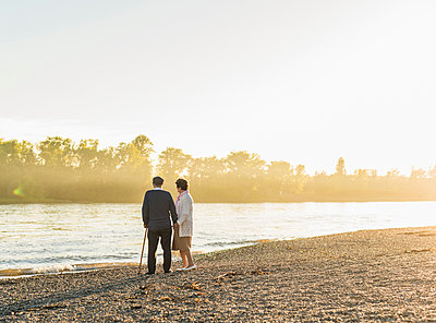 Senior couple standing on at riverside by sunset - p300m1460683 by Uwe Umstätter