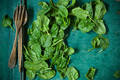 Spinach leaves and salad cutlery on green background - p300m1588005 von Achim Sass