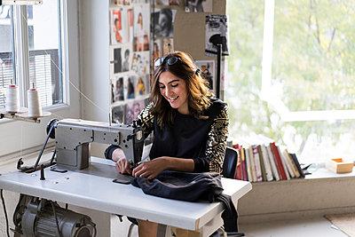 Smiling young fashion designer using sewing machine in her atelier - p300m2068723 von VITTA GALLERY