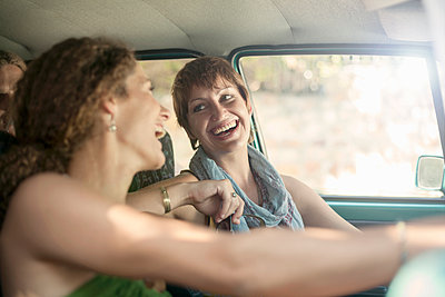 Smiling friends sitting in car during road trip - p300m2224995 by LOUIS CHRISTIAN