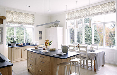 Open plan kitchen and dining area in country house - p349m790373 by Brent Darby