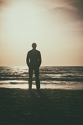 Man standing alone on the beach  - p794m1088243 by Mohamad Itani