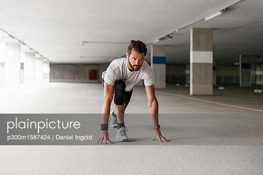 Athlete in starting position in parking garage - p300m1587424 von Daniel Ingold